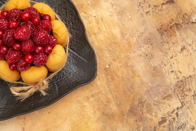 Vista superior de um bolo de presente com frutas no lado direito de um fundo de cor mista