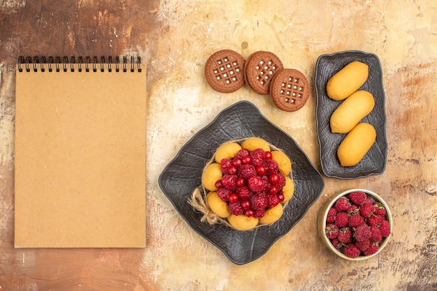 Vista superior de um bolo de presente e biscoitos em frutas de pratos marrons e caderno na mesa de cores misturadas