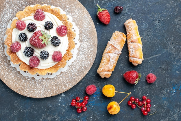 Vista superior de um bolo delicioso com creme de açúcar em pó e frutas vermelhas junto com pulseiras na mesa escura, biscoito de bolo de frutas vermelhas