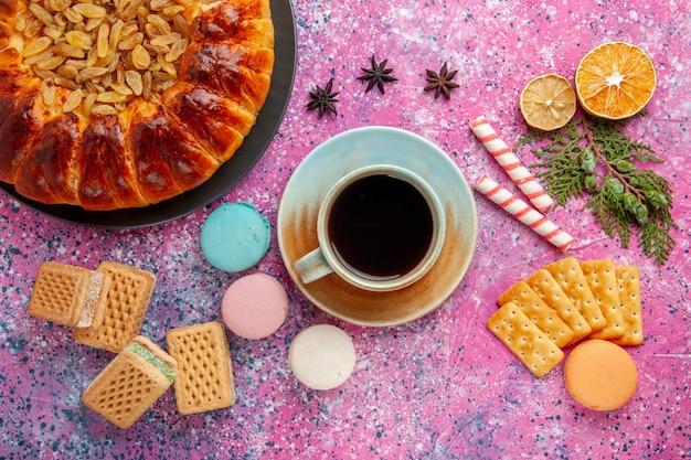 Vista superior de um bolo delicioso com passas, waffles de chá e biscoitos na mesa rosa