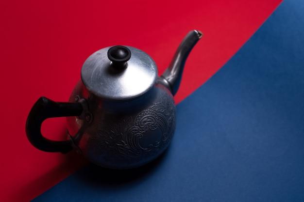 Vista superior de um bule de alumínio vintage, em duas superfícies escuras de cores vermelhas e azuis