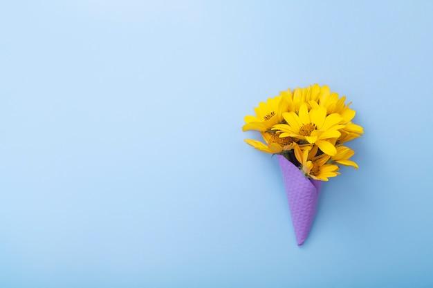 Vista superior de um buquê de flores amarelas em um cone de waffle roxo
