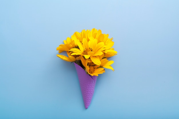 Vista superior de um buquê de flores amarelas em um cone roxo