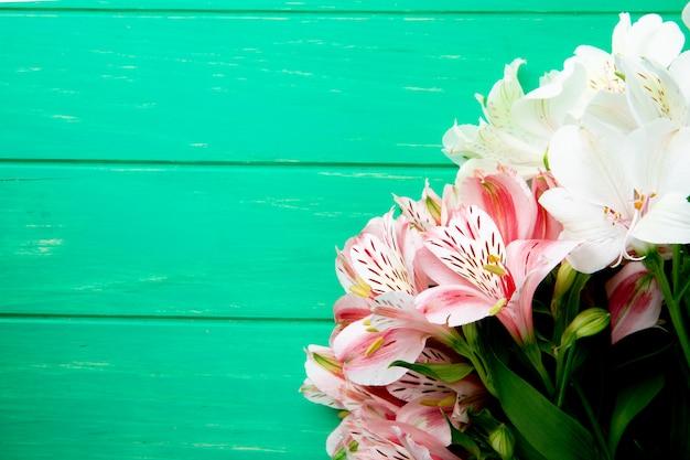 Vista superior de um buquê de flores de alstroemeria cor de rosa e branco deitado isolado sobre fundo verde de madeira, com espaço de cópia