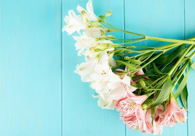 Vista superior de um buquê de flores de alstroemeria cor de rosa e branco sobre fundo azul de madeira com espaço de cópia