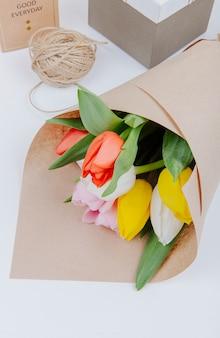 Vista superior de um buquê de flores de tulipa colorida em um papel artesanal com caixas de presente e corda no fundo branco