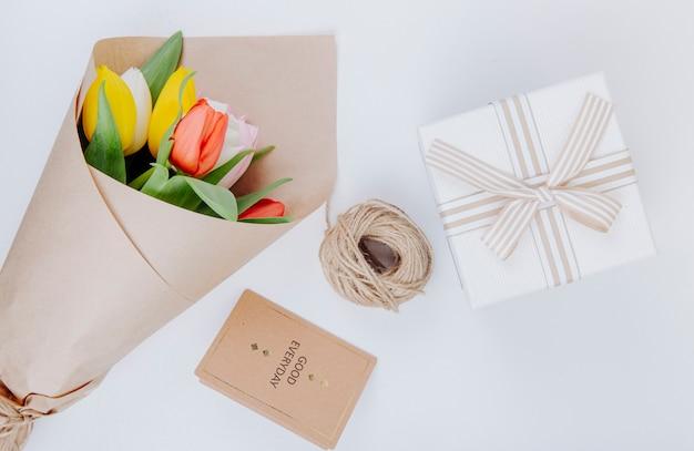 Vista superior de um buquê de flores de tulipa colorida em um papel artesanal com uma caixa de presente de cartão postal e corda no fundo branco
