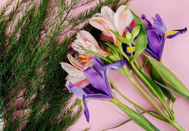 Vista superior de um buquê de íris roxa escura e alstroemeria flores com aspargos no fundo rosa