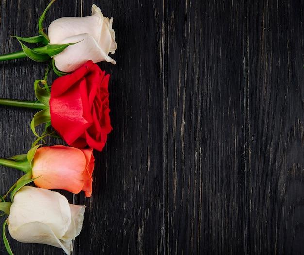 Vista superior de um buquê de rosas brancas de cor vermelha e coral, isolado no fundo escuro de madeira com espaço de cópia