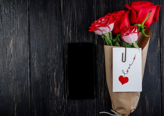Vista superior de um buquê de rosas de cor vermelha em papel ofício com cartão postal anexado e um smartphone no fundo escuro de madeira com espaço de cópia
