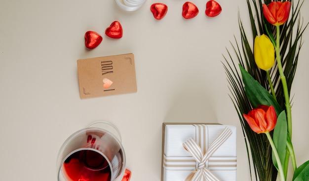 Vista superior de um buquê de tulipas com bombons de chocolate em forma de coração, embrulhados em papel alumínio vermelho, copo de vinho, cartão pequeno de papel pardo e uma caixa de presente na mesa branca