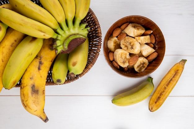 Vista superior de um cacho de frutas de banana em uma cesta de vime e uma tigela com bananas fatiadas e amêndoa em branco