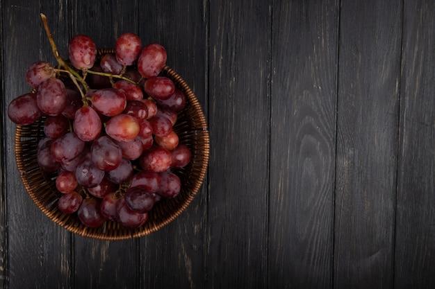 Vista superior de um cacho de uvas doces frescas em uma cesta de vime na mesa de madeira escura com espaço de cópia