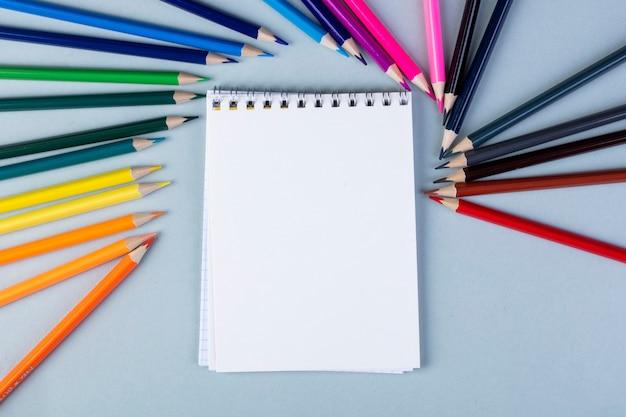 Vista superior de um caderno de desenho com lápis de cor, dispostos em branco