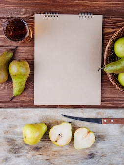 Vista superior de um caderno de desenho e peras frescas maduras com um copo de suco de pêra em fundo de madeira
