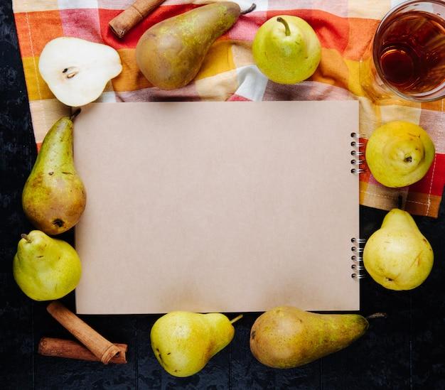 Vista superior de um caderno de desenho e peras maduras frescas, dispostas ao redor com um copo de suco de pêra em fundo preto