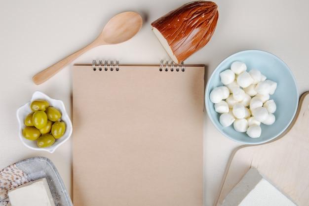 Vista superior de um caderno de desenho e vários tipos de queijo mini mussarela em uma tigela azul, queijo feta, defumado e queijo com azeitonas em conserva na mesa branca