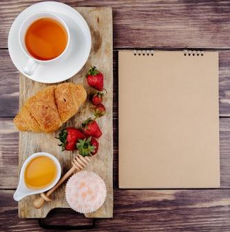 Vista superior de um caderno de desenho ee mel de croissant de morangos maduros frescos e uma xícara de chá em uma tábua de madeira no rústico