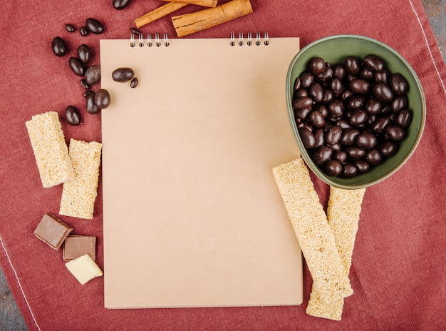 Vista superior de um caderno e doces de chocolate vidrados em uma tigela com pedaços de gergelim kozinaki na toalha de mesa rosa escuro