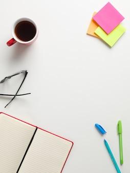 Vista superior de um caderno vermelho aberto, lembretes coloridos, caneta azul e verde