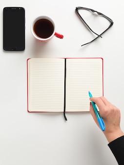 Vista superior de um caderno vermelho aberto, uma mão feminina segurando uma caneta azul
