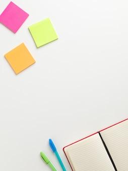 Vista superior de um caderno vermelho em branco aberto no canto inferior com uma caneta verde e uma caneta azul ao lado