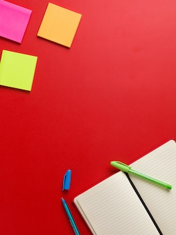 Vista superior de um caderno vermelho em branco aberto no canto inferior com uma caneta verde