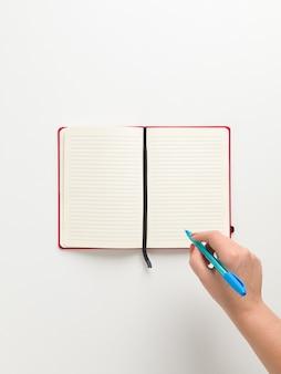 Vista superior de um caderno vermelho em branco aberto no centro e uma mão feminina segurando uma caneta azul