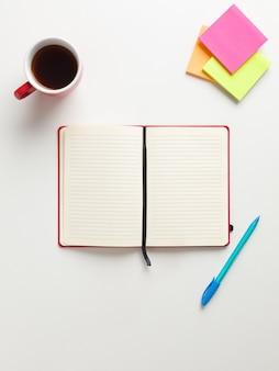 Vista superior de um caderno vermelho em branco aberto no centro, lembretes coloridos no canto superior