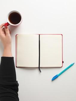 Vista superior de um caderno vermelho em branco aberto no centro, uma caneta azul ao lado e uma mão feminina