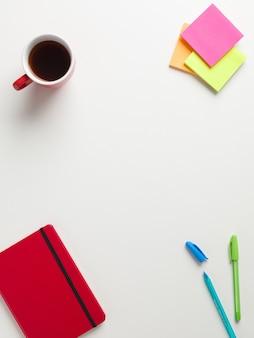 Vista superior de um caderno vermelho fechado, lembretes coloridos, caneta azul e verde,