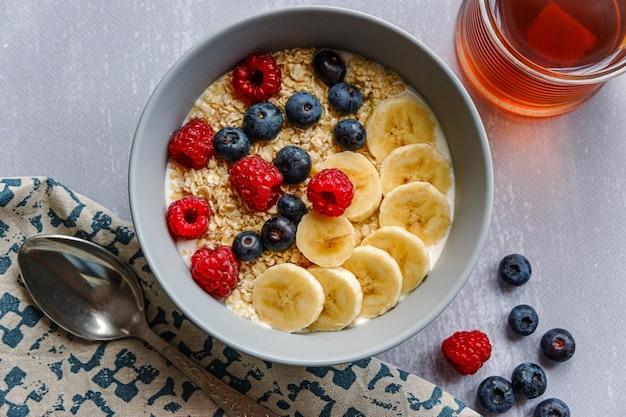 Vista superior de um café da manhã saudável com aveia em uma tigela, rodelas de banana, framboesa, mirtilo e uma xícara de chá na mesa cinza claro