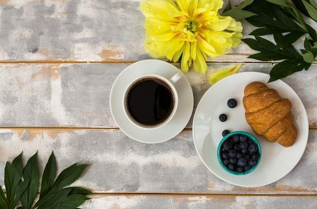 Vista superior de um café fresco com croissants e mirtilos e peônias