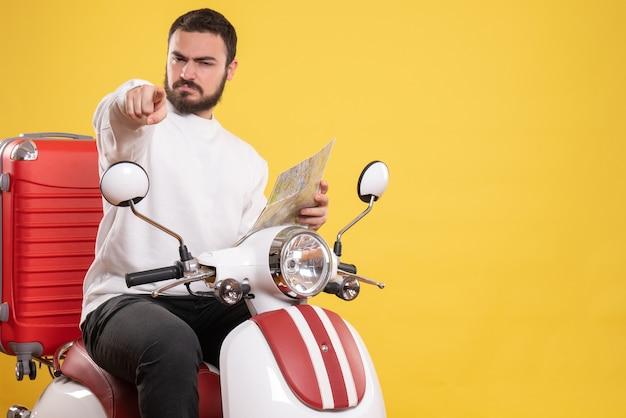 Vista superior de um cara confuso sentado em uma motocicleta com uma mala segurando um mapa apontando para a frente em um fundo amarelo isolado