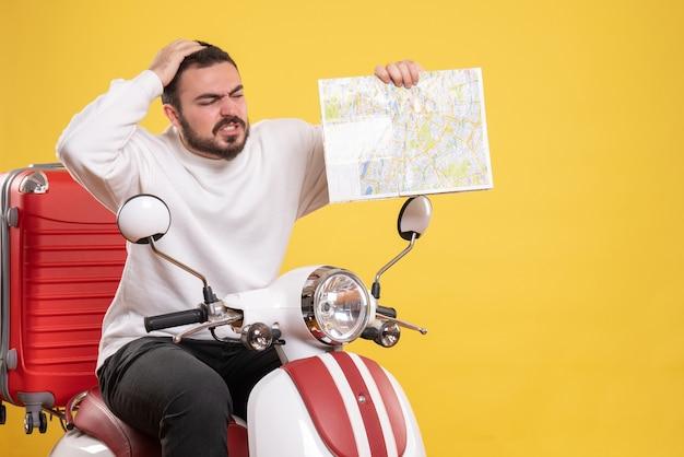 Vista superior de um cara confuso sentado em uma motocicleta com uma mala segurando um mapa em fundo amarelo isolado