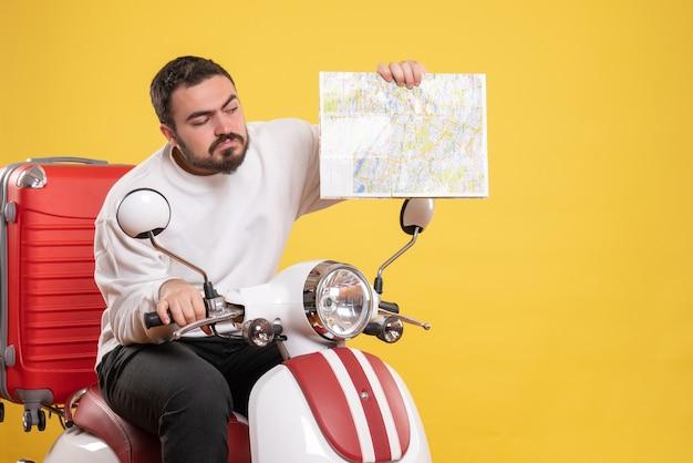 Vista superior de um cara curioso sentado em uma motocicleta com uma mala segurando um mapa em fundo amarelo isolado