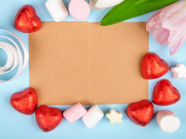 Vista superior de um cartão aberto de papel pardo com marshmallows espalhados e bombons de chocolate em forma de coração em folha vermelha com tulipas cor de rosa na mesa azul