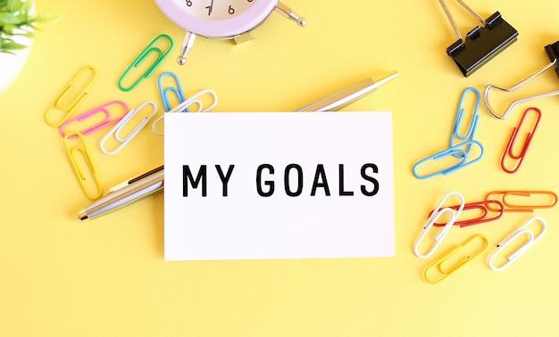 Vista superior de um cartão de visita com o texto meus objetivos, caneta, clipes de papel e relógio em uma mesa amarela. conceito de negócios.