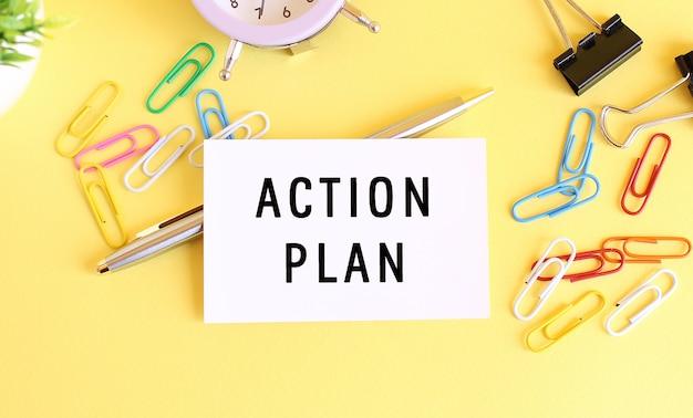 Vista superior de um cartão de visita com plano de ação de texto, caneta, clipes de papel e relógio em um fundo amarelo. conceito de negócios.