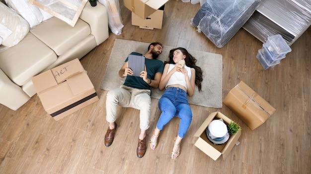 Vista superior de um casal apaixonado, deitado no chão, usando um tablet.