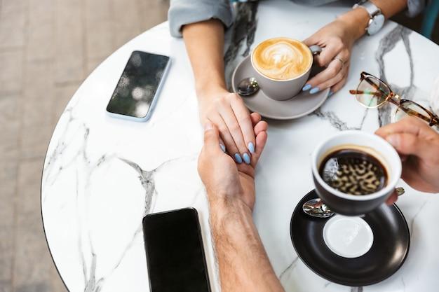 Vista superior de um casal apaixonado em um encontro sentado à mesa do café ao ar livre, bebendo café