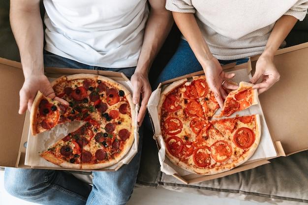 Vista superior de um casal comendo duas pizzas grandes em um sofá