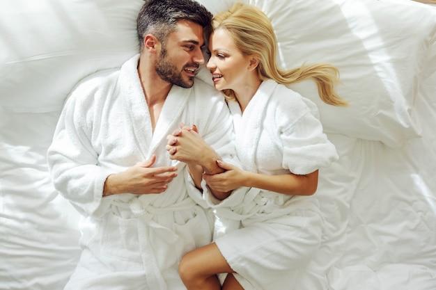 Vista superior de um casal de meia-idade apaixonado em roupões de banho na lua de mel, deitado em uma cama e abraçando.