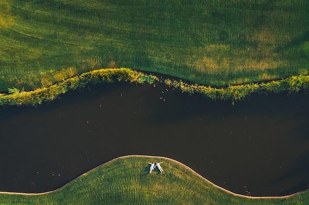 Vista superior de um casal deitado na grama perto do rio