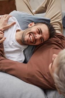 Vista superior de um casal gay contemporâneo rindo alegremente enquanto relaxa no sofá em casa
