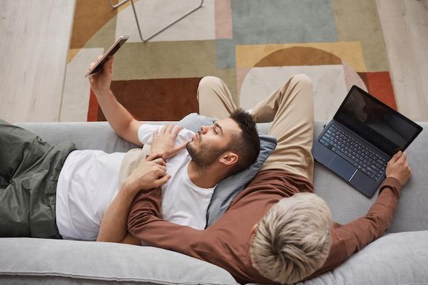 Vista superior de um casal gay contemporâneo usando computadores enquanto relaxam no sofá juntos em um interior mínimo de casa, copie o espaço