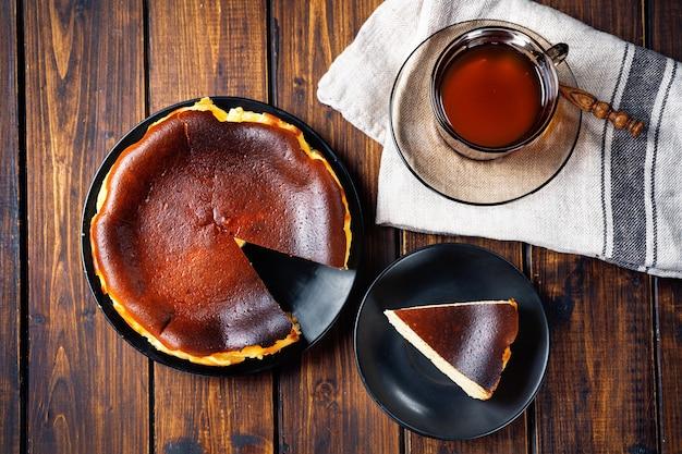 Vista superior de um cheesecake queimado basco moderno e uma xícara de chá