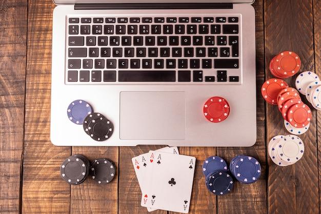 Vista superior de um computador com fichas de pôquer e cartões para apostas ou jogar.