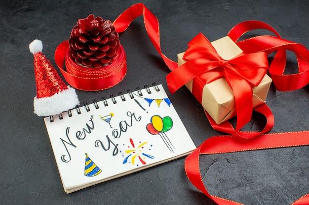 Vista superior de um cone de conífera de presente com fita vermelha e caderno com a escrita de ano novo e chapéu de papai noel lindo presente em fundo escuro