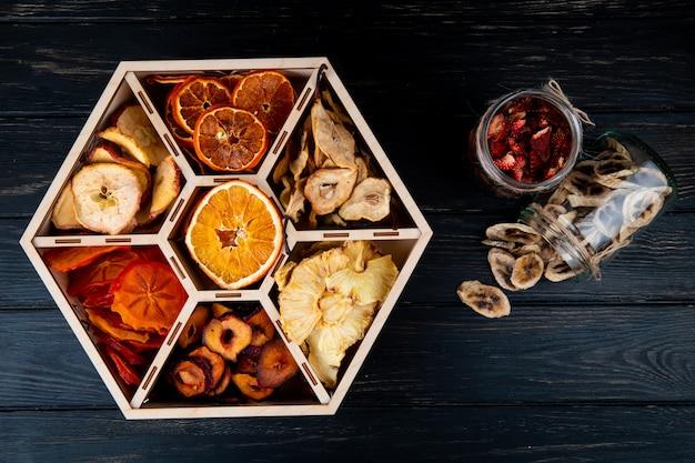 Vista superior de um conjunto de frutas secas em uma caixa de madeira e banana seca e lascas de morango em potes de vidro no fundo preto